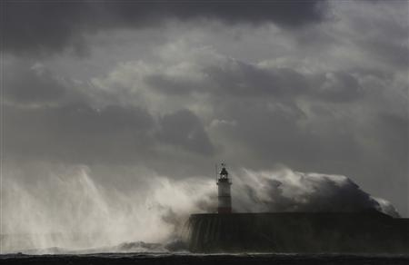 Waves crash against a lighthouse during storms that battered Britain and where a 14-year-old boy was swept away to sea, at Newhaven in South East England October 28, 2013. REUTERS/Luke MacGregor